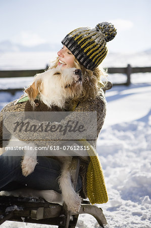 Woman embracing pet dog in snow Stock Photo - Premium Royalty-Free, Image code: 618-07612315