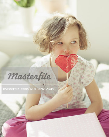Young girl enjoying heart shaped lolly Stock Photo - Premium Royalty-Free, Image code: 618-07612349
