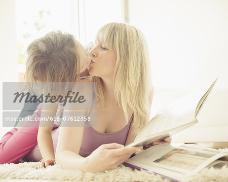 Young girl kissing mother on rug Stock Photo - Premium Royalty-Free, Image code: 618-07612358