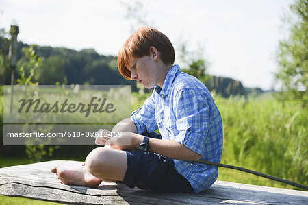 Boy carving wood on riverbank Stock Photo - Premium Royalty-Free, Image code: 618-07612469