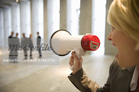 Businesswoman shouting to colleagues through bullhorn in lobby Stock Photo - Premium Royalty-Free, Image code: 618-07653710