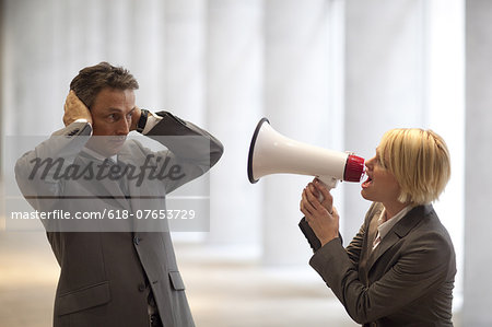 Businesswoman shouting through bullhorn to colleague Stock Photo - Premium Royalty-Free, Image code: 618-07653729