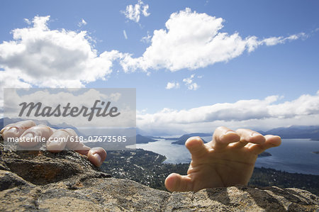 Person's hand grasp summit rocks, lake below Stock Photo - Premium Royalty-Free, Image code: 618-07673585