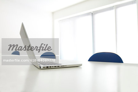 Still life of laptop on boardroom table Stock Photo - Premium Royalty-Free, Image code: 618-08389278