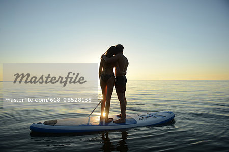 Teenage couple watching sunset from paddleboard on Lake Starnberg, Bavaria, Germany, Europe Stock Photo - Premium Royalty-Free, Image code: 618-08528138