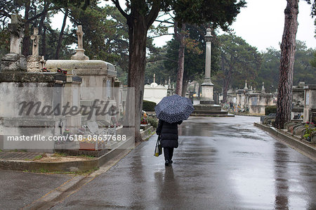 senior woman with an umbrella in the cemetery Stock Photo - Premium Royalty-Free, Image code: 618-08637688