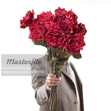 suitor presenting bouquet of red flowers Stock Photo - Premium Royalty-Free, Image code: 621-00787724