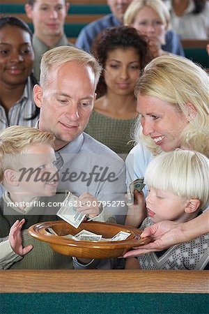 Family in Church Putting Money in Offering Plate Stock Photo - Premium Royalty-Free, Image code: 621-00795275