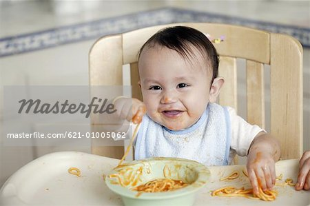 Baby eating in high chair Stock Photo - Premium Royalty-Free, Image code: 621-01005062