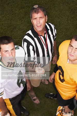 Referee tossing coin in front of football players Stock Photo - Premium Royalty-Free, Image code: 621-01201393