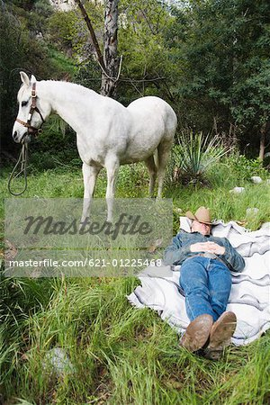 Cowboy sleeping near horse Stock Photo - Premium Royalty-Free, Image code: 621-01225468