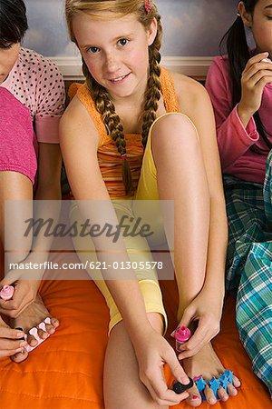 Preteen girls painting toenails