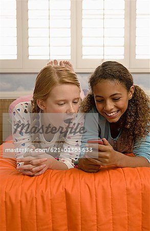 Preteen girls reacting to text message Stock Photo - Premium Royalty-Free, Image code: 621-01305633
