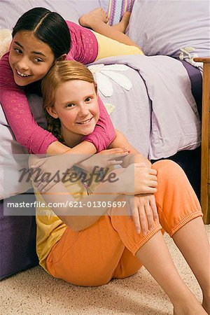 Preteen girls in pajamas embracing