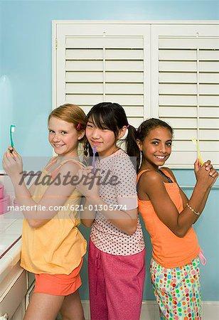 Three preteen girls posing with toothbrushes Stock Photo - Premium ...