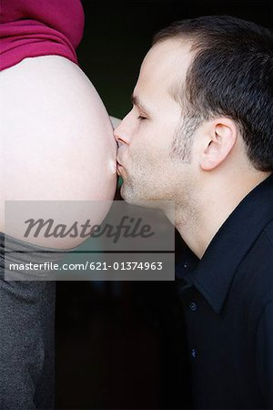 Man kissing pregnant stomach Stock Photo - Premium Royalty-Free, Image code: 621-01374963