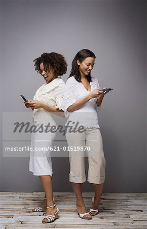 Women text messaging Stock Photo - Premium Royalty-Free, Image code: 621-01519870