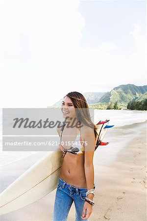 Teenage girl carrying surfboard Stock Photo - Premium Royalty-Free, Image code: 621-01554375