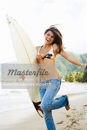 Happy teenage girl holding surfboard Stock Photo - Premium Royalty-Free, Image code: 621-01554377