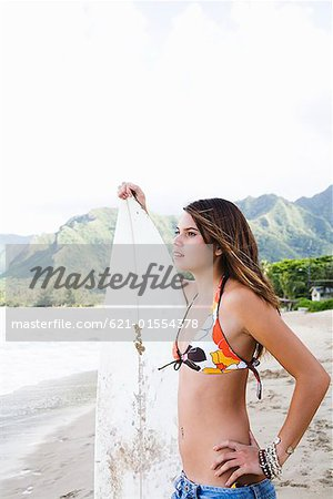 Pensive teenage girl holding surfboard Stock Photo - Premium Royalty-Free, Image code: 621-01554378