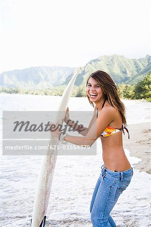 Laughing teenage girl holding surfboard Stock Photo - Premium Royalty-Free, Image code: 621-01554379