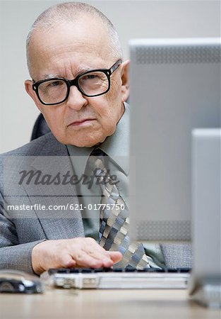 Grumpy senior man sitting at desk Stock Photo - Premium Royalty-Free, Image code: 621-01775750