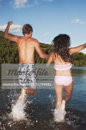 Teen couple running into lake Stock Photo - Premium Royalty-Free, Image code: 621-01799881