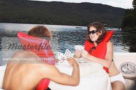 Teenage couple on boat playing cards Stock Photo - Premium Royalty-Free, Image code: 621-01799959