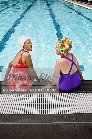 Smiling senior woman swimmers seated at pool edge Stock Photo - Premium Royalty-Free, Image code: 621-01800087