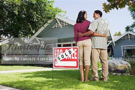 Couple with sold sign and house Stock Photo - Premium Royalty-Free, Image code: 621-01800309