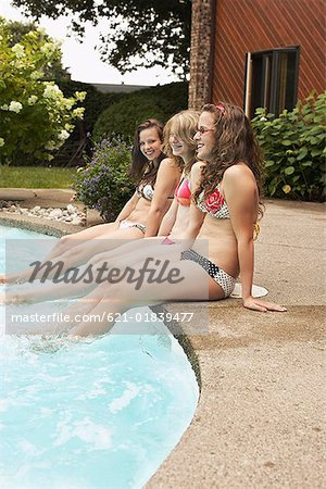 Teenage girls sitting at poolside Stock Photo - Premium Royalty-Free, Image code: 621-01839477