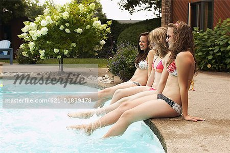 Teenage girls sitting at poolside Stock Photo - Premium Royalty-Free, Image code: 621-01839478