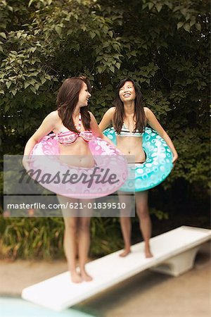 Teenage girls with swim rings Stock Photo - Premium Royalty-Free, Image code: 621-01839510