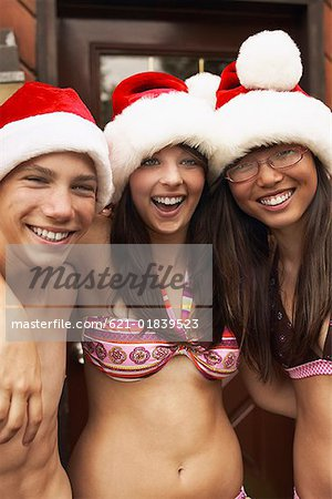 Teenagers wearing Santa Claus hats and swimwear Stock Photo - Premium Royalty-Free, Image code: 621-01839523