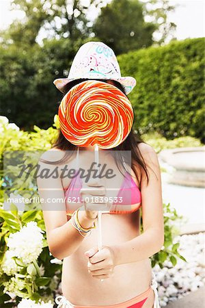 Teenage girl covering face with lollipop Stock Photo - Premium Royalty-Free, Image code: 621-01839533
