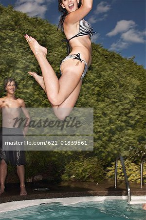 Teenage girl jumping into pool Stock Photo - Premium Royalty-Free, Image code: 621-01839561