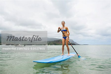 Woman on surfboard with paddle Stock Photo - Premium Royalty-Free, Image code: 621-02027905