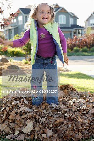 Smiling girl jumping in pile of leafs Stock Photo - Premium Royalty-Free, Image code: 621-02085257