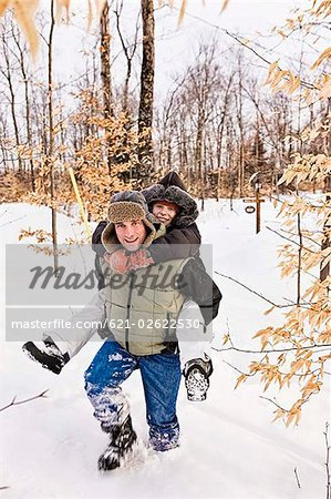 Father giving daughter piggyback ride in snow Stock Photo - Premium Royalty-Free, Image code: 621-02622530
