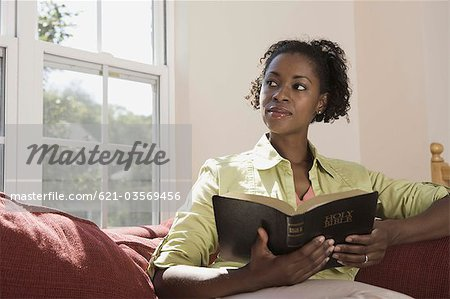 Woman holding Holy Bible indoors Stock Photo - Premium Royalty-Free, Image code: 621-03569456