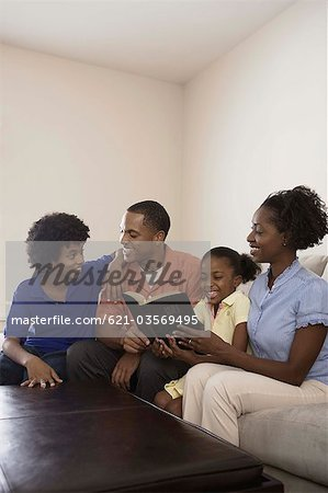 Family sitting on couch and reading Holy Bible Stock Photo - Premium Royalty-Free, Image code: 621-03569495