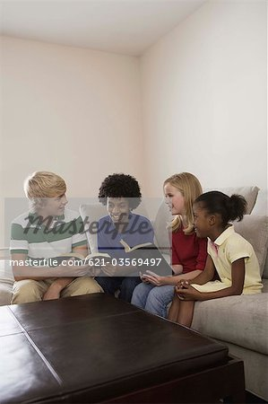 Children sitting on couch and reading Holy Bible Stock Photo - Premium Royalty-Free, Image code: 621-03569497