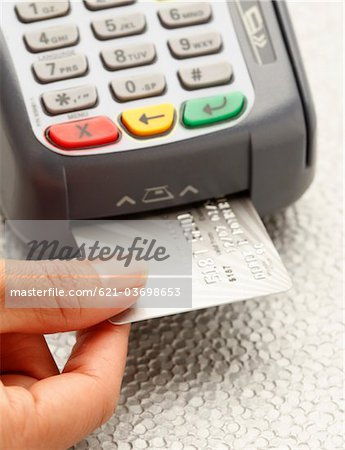 Hand inserting credit card into machine Stock Photo - Premium Royalty-Free, Image code: 621-03698653