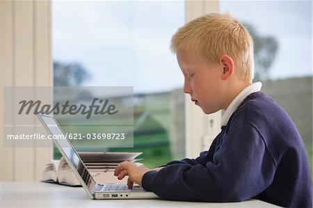 profile of school boy working on laptop at a desk Stock Photo - Premium Royalty-Free, Image code: 621-03698723