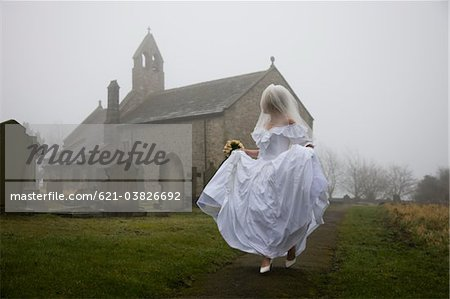 bride running away from a church Stock Photo - Premium Royalty-Free, Image code: 621-03826692