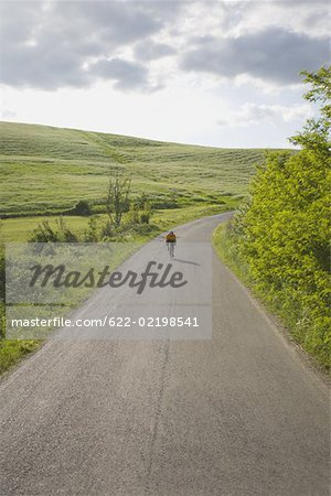 Cyclist on road through hills Stock Photo - Premium Royalty-Free, Image code: 622-02198541