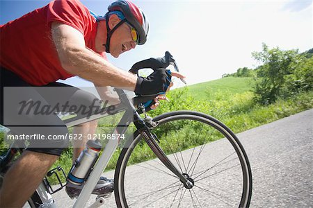 Side view of a man cycling on road Stock Photo - Premium Royalty-Free, Image code: 622-02198574