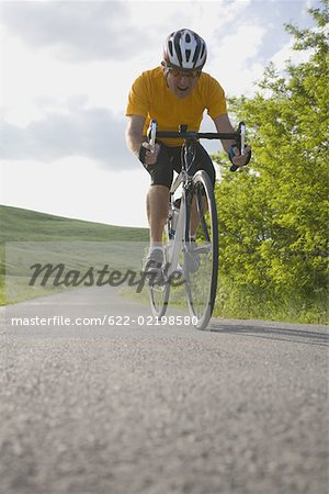 Front view of a man cycling on road Stock Photo - Premium Royalty-Free, Image code: 622-02198580