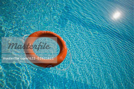 An orange life ring floating in water Stock Photo - Premium Royalty-Free, Image code: 622-02621621