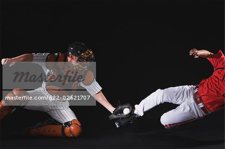 Baseball player sliding into a base Stock Photo - Premium Royalty-Free, Image code: 622-02621707